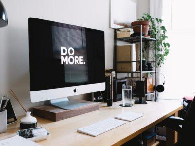 """Stanowisko do pracy zdalnej i komputer z napisem """"do more"""""""